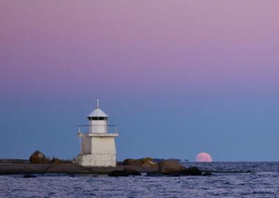 Kuu nousee loiston takaa Suomenlahdella.
